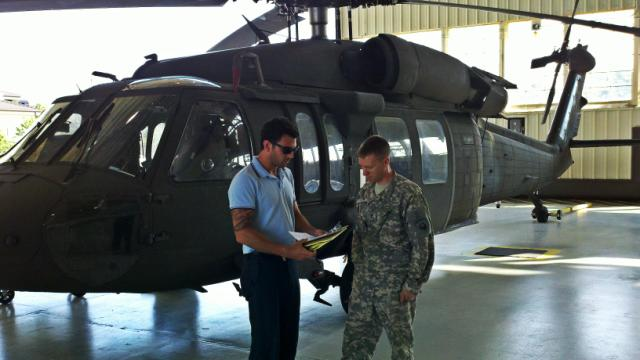 Galyon going over the results of an energy audit of one of the aircraft hangars with Sgt. Linder, the command's Building Energy Manager